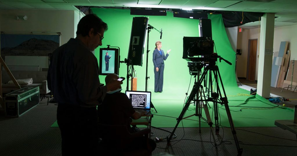 a woman standing in front of a green screen for a film crew
