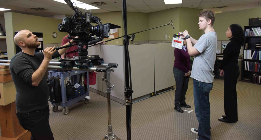 two members of a video production team shooting a corporate video in an office setting
